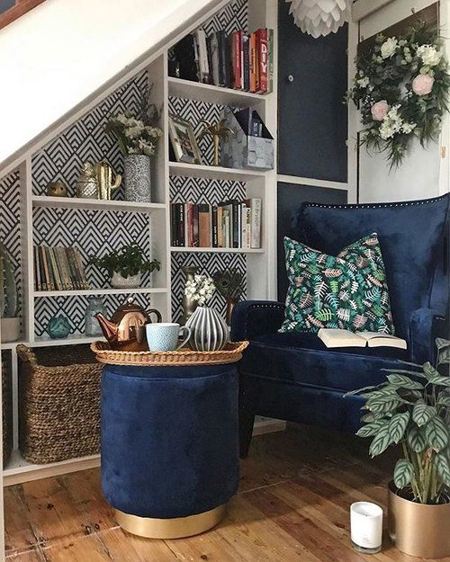 a little reading nook under the stairs includes a navy chair and ottoman, some built-in shelves, lamps and greenery