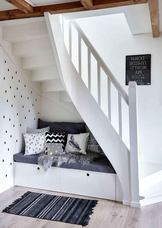 a storage bench with pillows and faux fur will form a cozy little under the stairs sitting nook