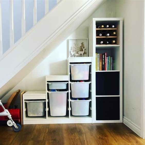 place an IKEA Kallax shelving unit under the stairs to get much storage space without any effort