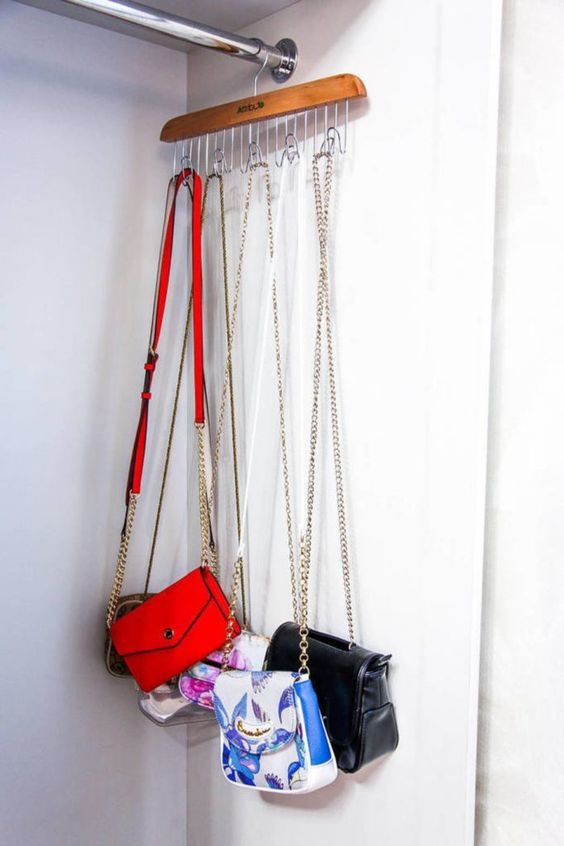 a clothes hanger with several hooks will hold all the crossbody bags you have without wasting any space