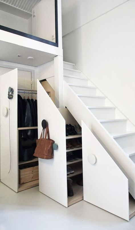 a hidden closet in the staircase can be completed with large round hooks where you can hang your bags