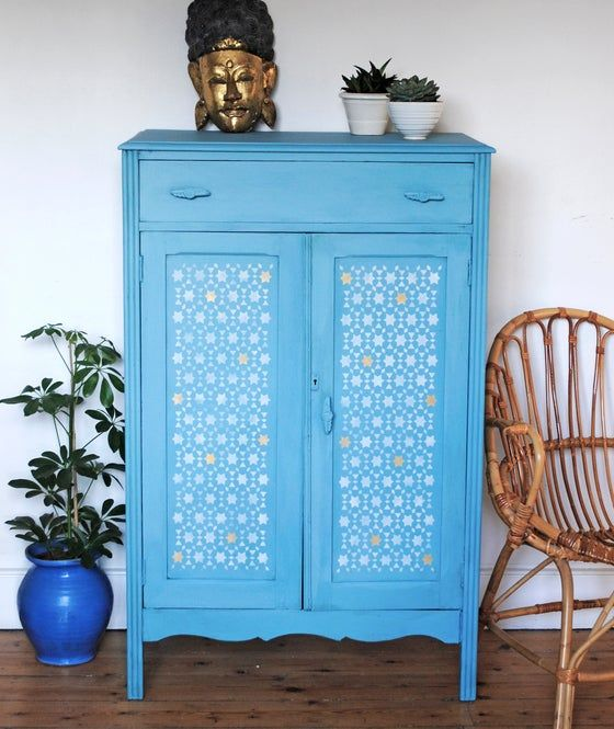 a blue dresser stenciled with white and yellow paint looks pretty and very catchy, it will make a statement
