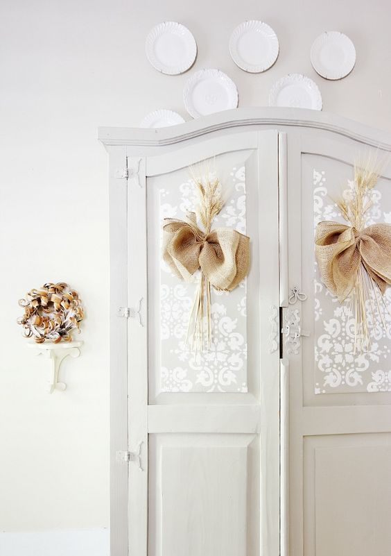 a dove grey wardrobe with white paint stenciling and burlap bows for a cozy rustic feel