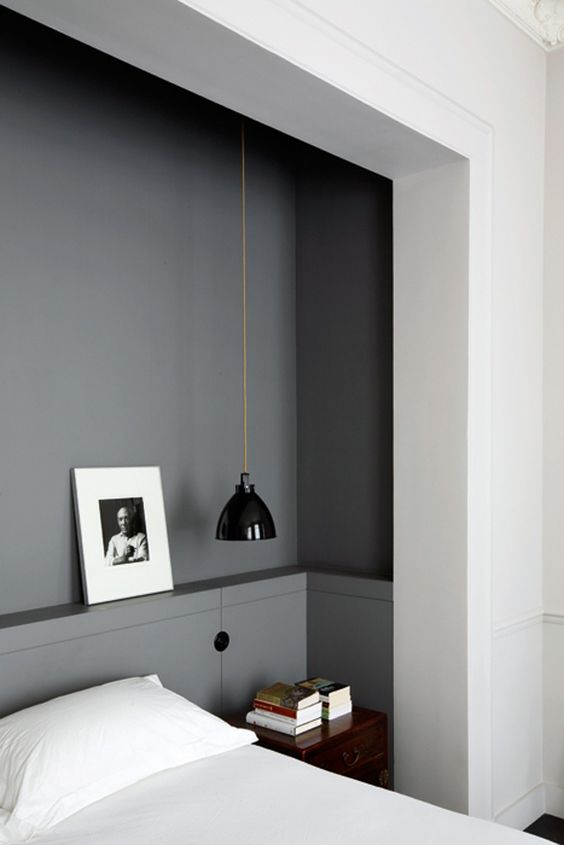 a mid-century modern black lamp looks great in a grey manly bedroom and its laconic design perfectly matches