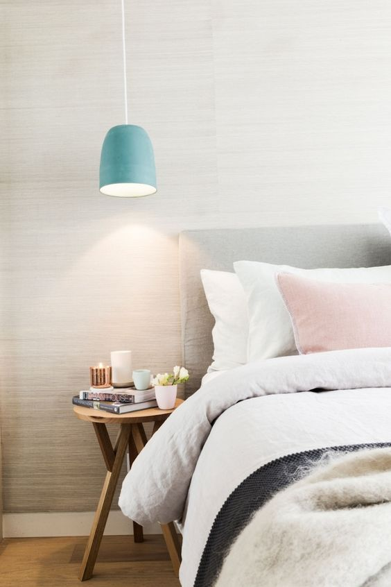 a muted blue pendant lamp adds a slight color touch to the space and matches stylish bedroom decor