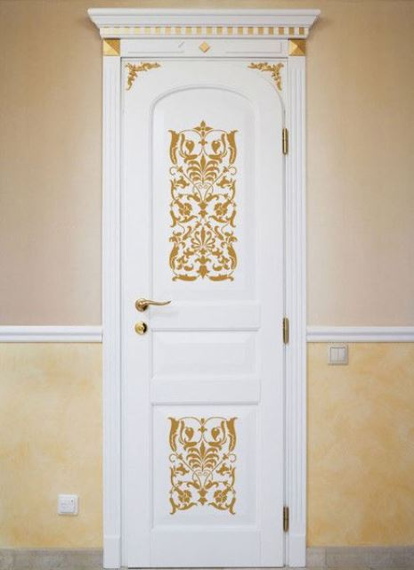 a white door with gold ornate stencils and a gold handle looks very chic and very stylish
