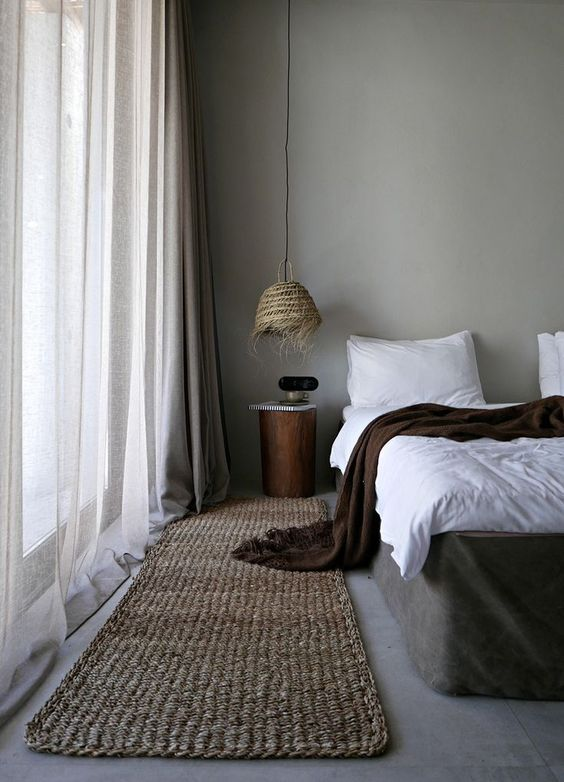 a wicker pendant lamp with fringe is a very rustic and coastal touch to the bedroom, a jute rug matches