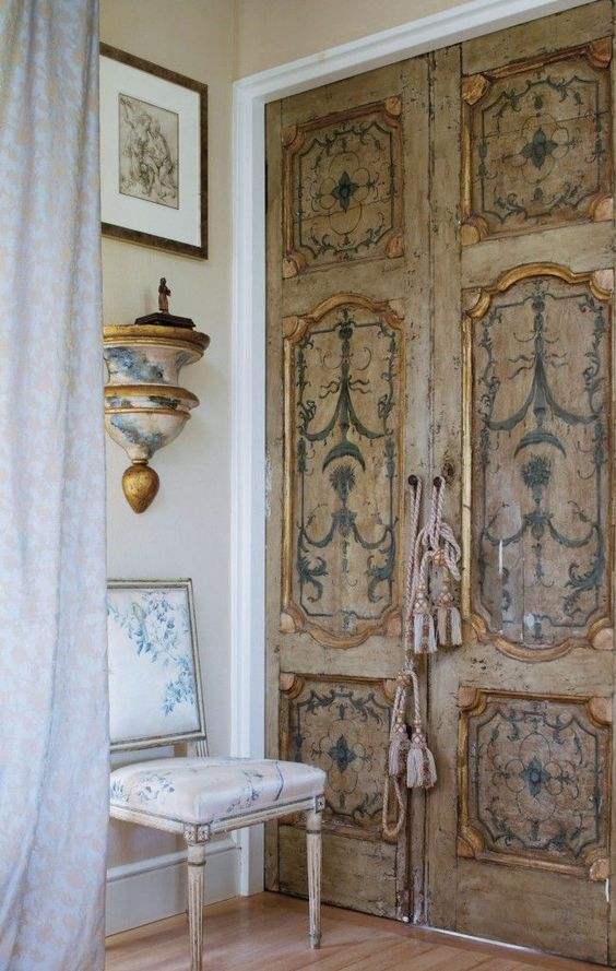 antique shabby doors spruced up with blue stencils that are repeated on furniture and lamps