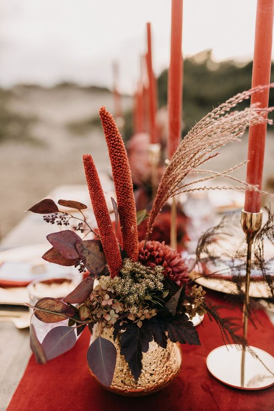 a bold fall wedding centerpiece in a gold vase, with burgundy blooms, greenery and dark foliage plus red candles