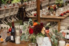 a bold fall wedding tablescape with a lush floral centerpiece, candles, pomegranates and burgundy napkins
