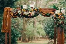 a bright fall wedding arch with mustard velvet, bright and white blooms, foliage and candle lanterns