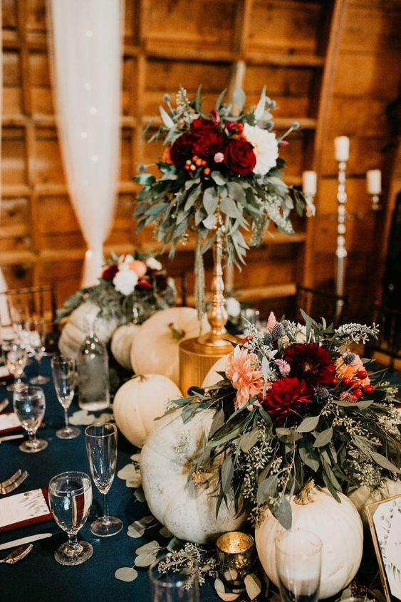 a bright fall wedding centerpiece of white pumpkins, bright flowers on a stand and candles