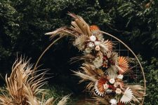 a chic modern boho wedding arch decorated with dried colorful leaves and fronds and pastel blooms