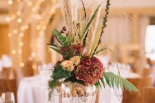 a chic wedding centerpiece of a mercury glass vase and rust and red blooms, pampas grass and ferns