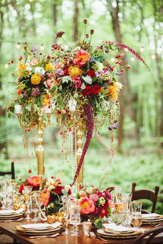 a colorful floral centerpiece of cascading blooms and greenery of various colors for a woodland wedding