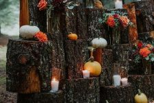 a fall wedding altar of tree stumps, candles and pumpkins plus bright and dark fall blooms wows