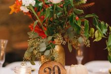 a fall wedding centerpiece of a wood slice, pumpkins, candles and bright fall blooms in a gold jar