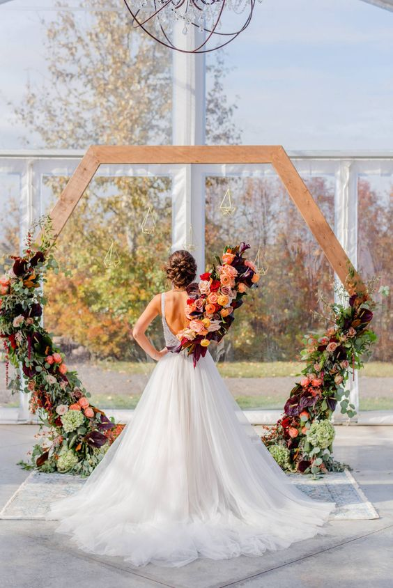 a hexagon wedding arch decorated with lush greenery, dark blooms and white and green ones for a fall ceremony