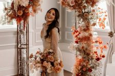 a lush and bold fall wedding arch decorated with bright fall-colored blooms, white florals, dried elements and pampas grass