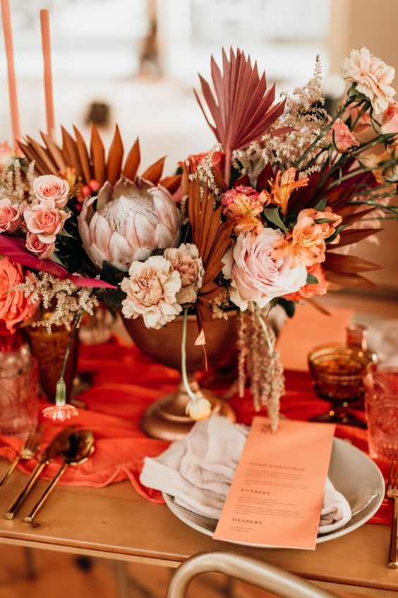 a modern fall wedding centerpiece of pastel and bright florals and dried and painted fronds
