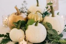 a neutral fall wedding centerpiece of white pumpkins, greenery and candles in polka dot candleholders