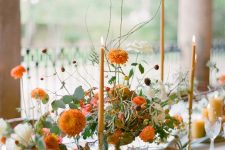 a pretty fall wedding centerpiece of white and orange blooms, greenery and orange candles is refined and chic