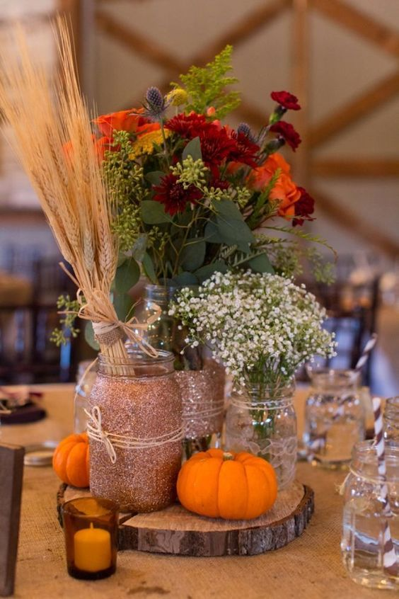 a rustic fall centerpiece of a wood slice, pumpkins, candles, bright blooms, baby's breath and a wheat bundle