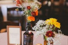 a rustic fall centerpiece of books, pumpkins, bright blooms in bottles is a lovely idea to rock