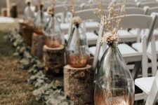 a rustic fall wedding arch with tree stumps, vases with dried grasses and blooms and eucalyptus