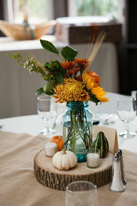 a rustic fall wedding centerpiece of a wood slice, candles, pumpkins and bright fall blooms and wheat in a jar