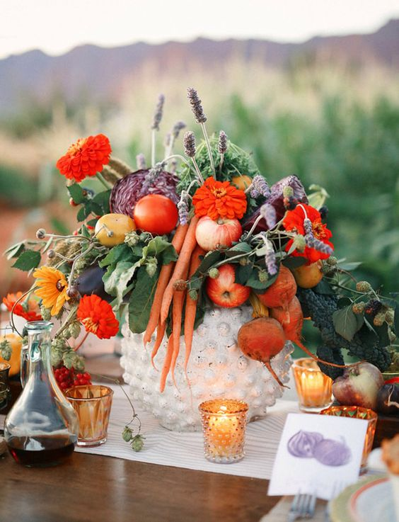a rustic fall wedding centerpiece with apples, radish and carrots plus lavender and some blooms