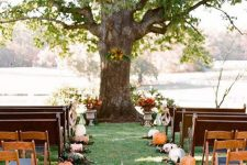 a rustic fall wedding ceremony space done with pumpkins and foliage plus fall blooms in vintage urns