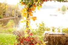 a rustic wedding arch placed in buckets and decorated with bright fall foliage and greenery