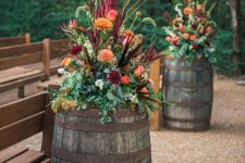 super bright and dimensional fall florla arrangements with greenery, twigs and feathers are amazing for aisle decor