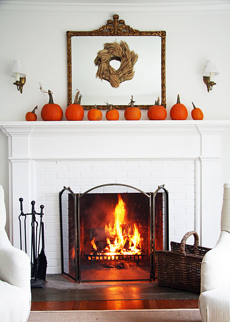 Single line of pumpkins and a wheat wreath is an easy and quick way to get yourself a simple fall display on a mantel.