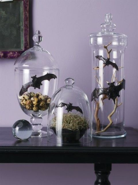 Halloween decor in jars and cloches, with hay, bats, branches and faux eggs is very chic and creative