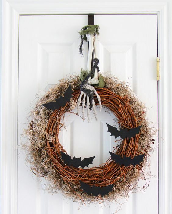 a Halloween wreath with moss and hay, bats, a skeleton hand and leaves for front door decor