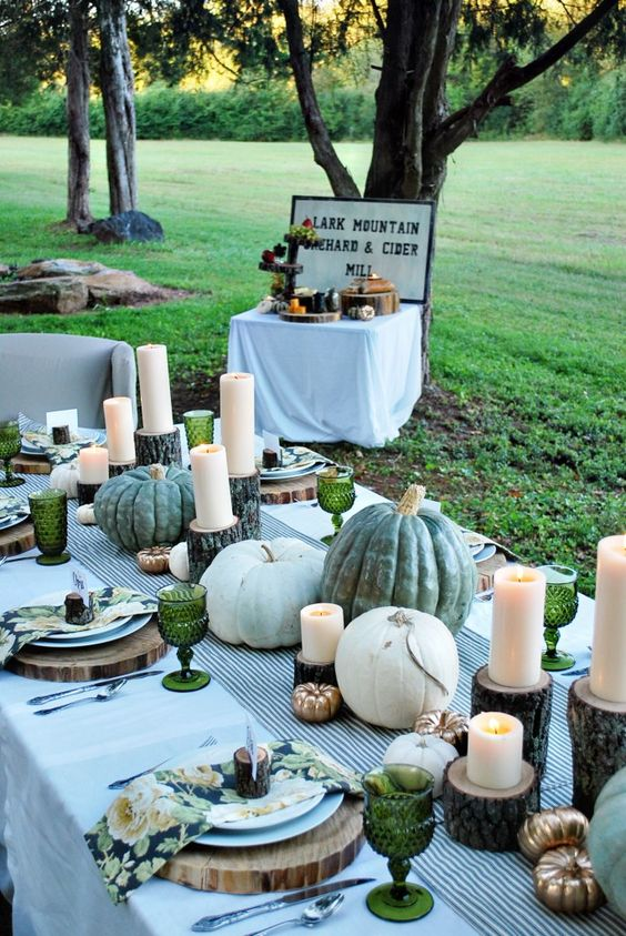 a beautiful green tablescape with a striped runner, floral napkins, wood slice placemats, neutral pumpkins and green goblets