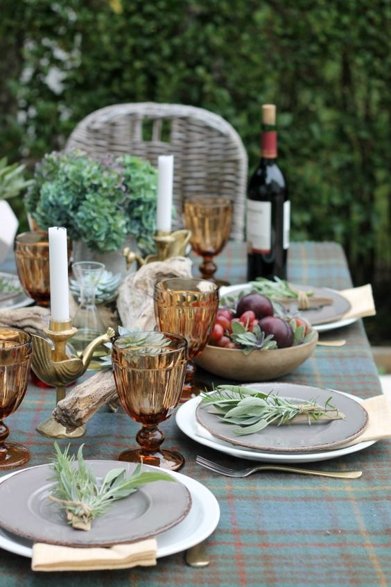 a beautiful outdoor fall tablescape with a plaid tablecloth, amber goblets, driftwood, greenery, gold touches and plates