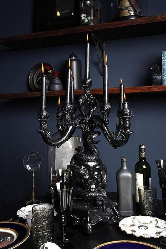a black skull covered with a snake candelabra with black candles is an adorable decoration to rock