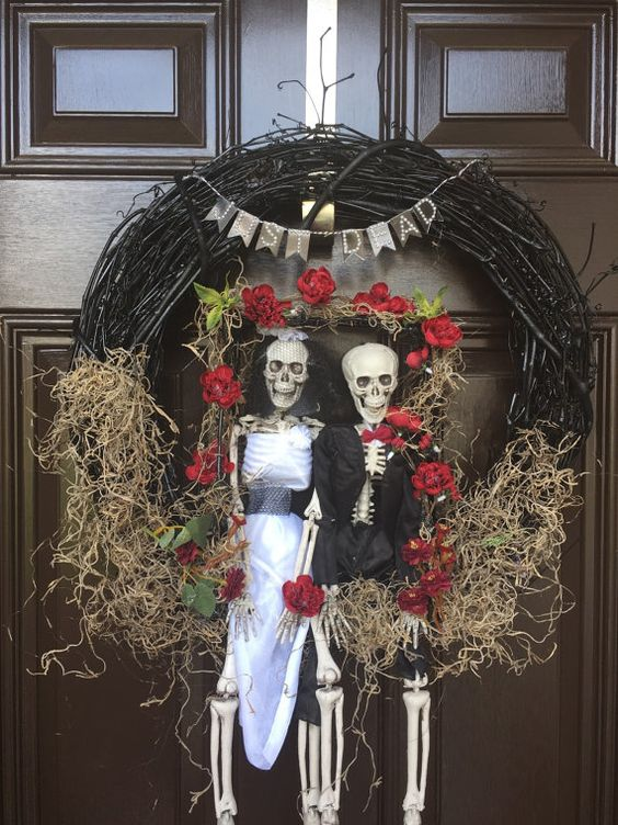 a black vine wreath with hay, blooms, a bunting and skeletons dressed in a chic way will decorate your front door for Halloween