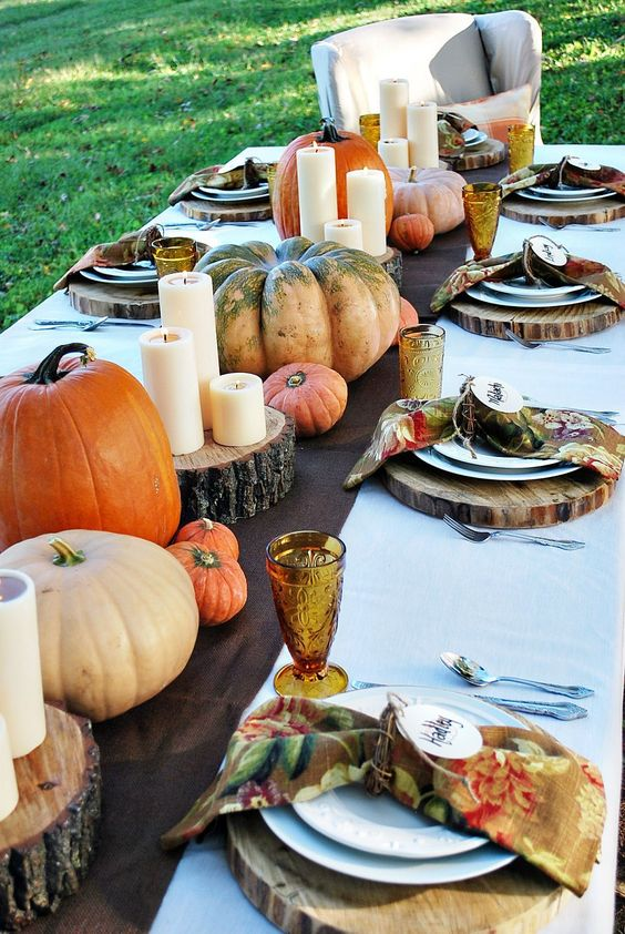 a bold fall table setting with a brown runner, wood slice placemats, natural bright pumpkins and candles and bold napkins