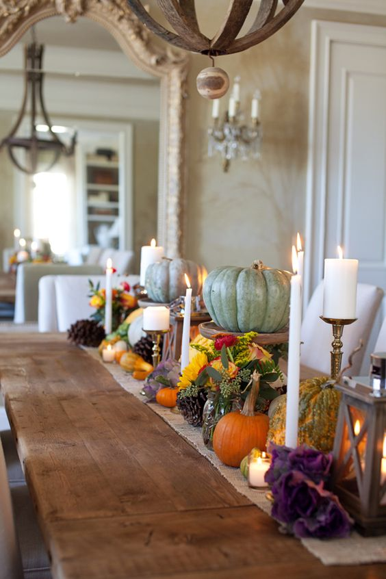 a bright fall tablescape with a burlap runner, bright blooms, natural pumpkins, pinecones and candles is very bold