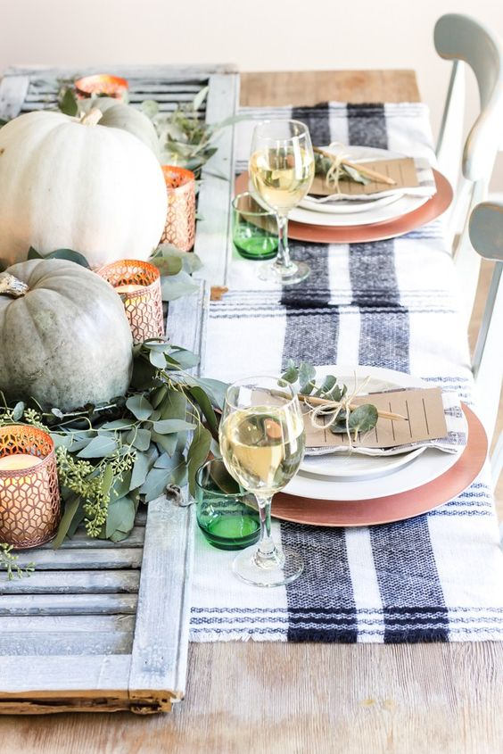 a bright fall tablescape with a wooden board, pumpkins, copper candleholders, copper chargers and green glasses
