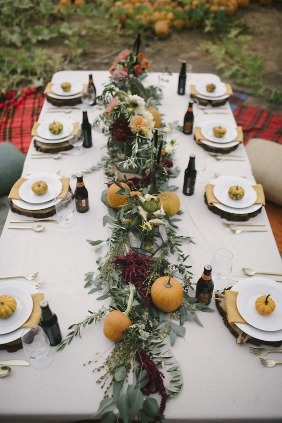 a chic fall tablescape with a lush greenery, pumpkin and flower runner, natural pumpkins and wood slice placemats