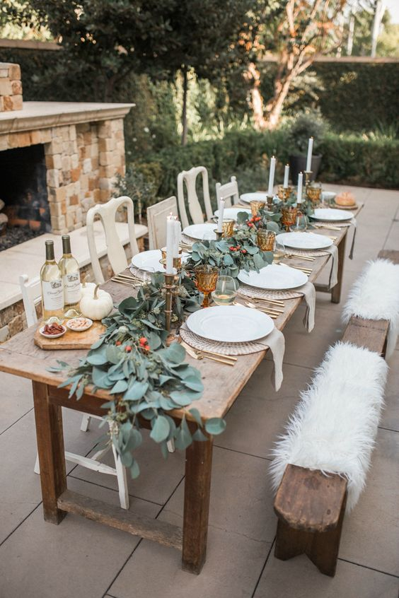 a chic outdoor fall tablescape with a greenery and berry runner, candles, amber goblets, white pumpkins and gold cutlery