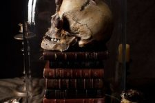a cloche with a stack of books, a skull and snails is a scary and creative Halloween decor idea