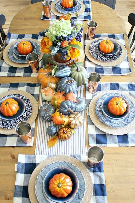 a copper and blue fall tablescape with a striped runner and plaid placemats, blue, metallic and rust pumpkins, leaves and copper glasses