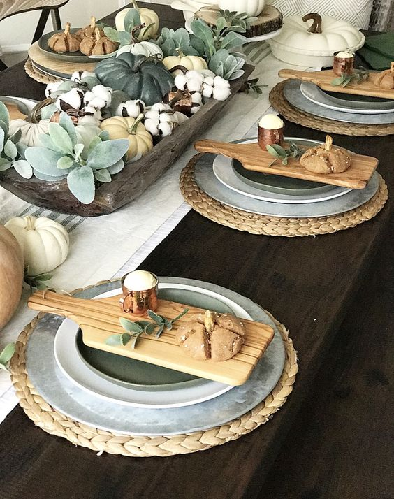 a cozy fall table setting with woven placemats, boards with food, pale greenery, cotton and natural napkins