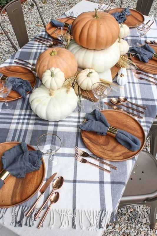 a cozy modern rustic tablescape with a plaid tablecloth, wooden plates, copper cutlery, natural pumpkins and wheat